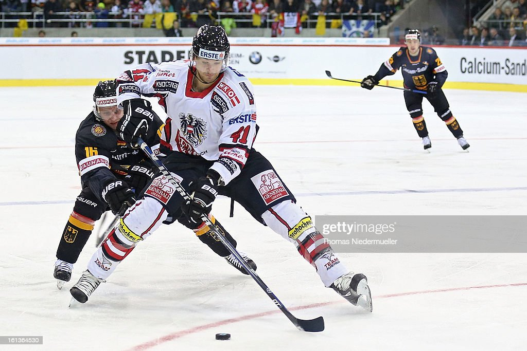 Michael Wolf (L) of Germany fights for the puck with Mario Altmann (R) of Austria during the Olympic Icehockey Qualifier match between Germany and Austria on February 10, 2013 in Bietigheim-Bissingen, Germany.