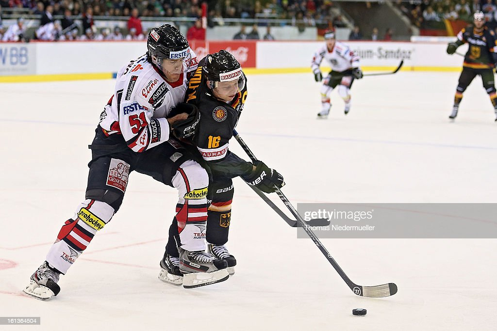 Michael Wolf (R) of Germany fights for the puck with Matthias Trattnig (L) of Austria during the Olympic Icehockey Qualifier match between Germany and Austria on February 10, 2013 in Bietigheim-Bissingen, Germany.