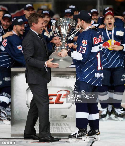 Michael Wolf of Muenchen receives the cup after winning the DEL PlayOffs Final Match 5 between EHC Muenchen and the Grizzlys Wolfsburg at Olympia...