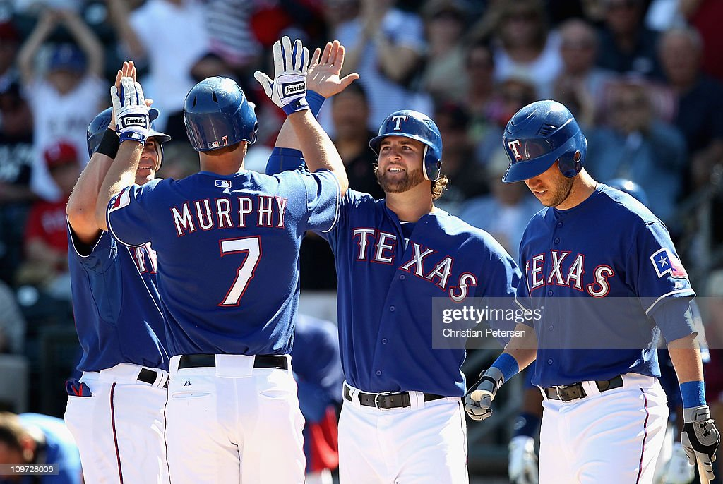 Michael Young and Mike Napoli of the Texas Rangers highfive teammate David Murphy after Murphy hit a 3 run home run against the Los Angeles Angels of...