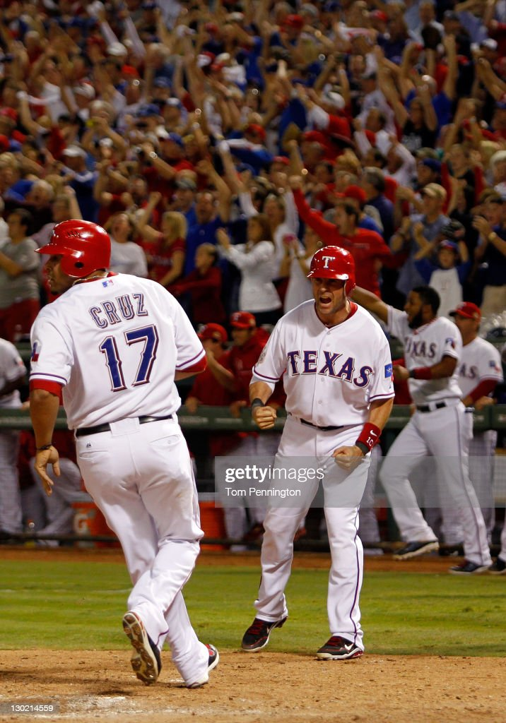 Michael Young and Nelson Cruz of the Texas Rangers celebrate after scoring on a Mike Napoli tworun double in the eighth inning during Game Five of...