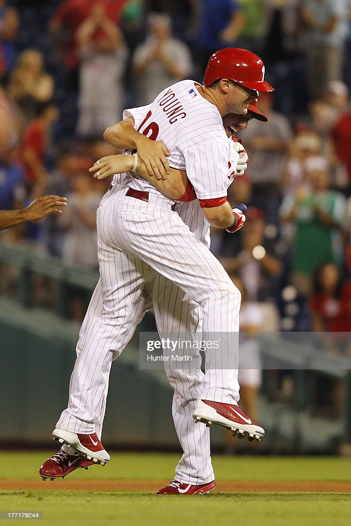Michael Young #10 of the Philadelphia Phillies gets a hug from Kevin Frandsen #28 after singling in the winning run in the ninth inning during a game against the Colorado Rockies at Citizens Bank Park on August 21, 2013 in Philadelphia, Pennsylvania. The Phillies won 4-3.