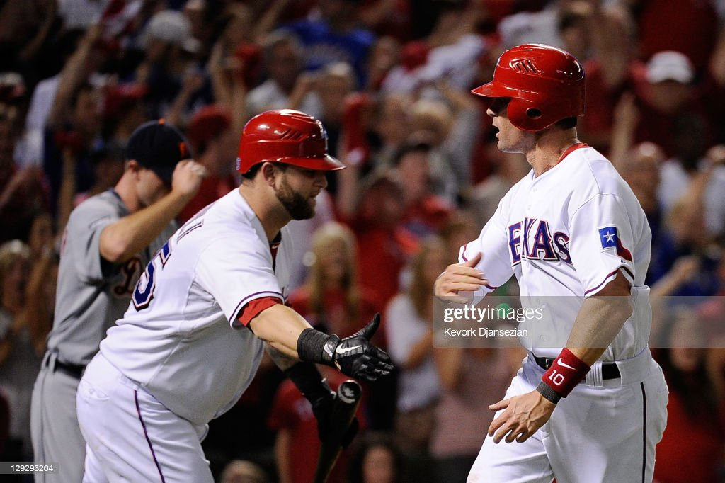 Michael Young of the Texas Rangers celebrates with Mike Napoli after scoring to take a 32 lead in the third inning of Game Six of the American League...