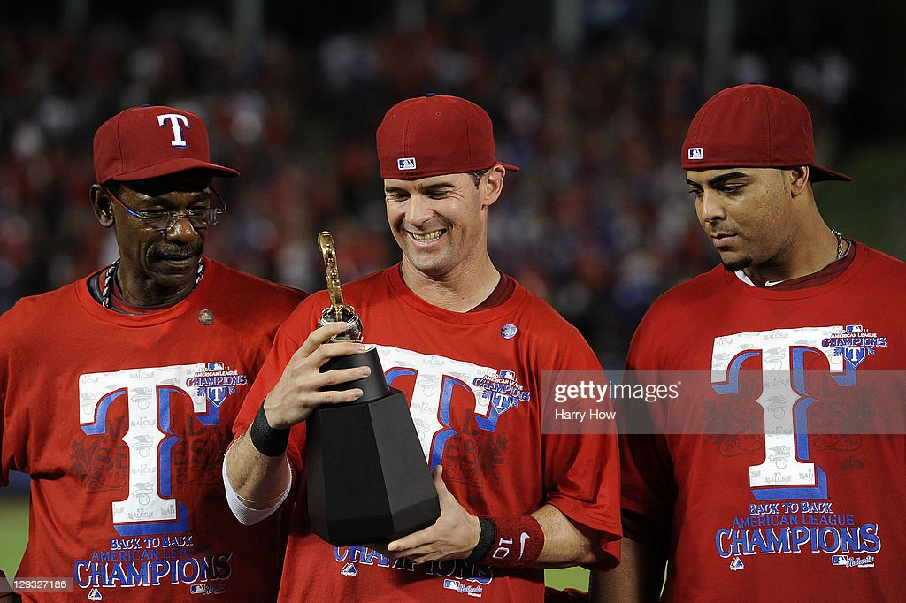 Michael Young of the Texas Rangers holds the William Harridge Award trophy on stage with manager Ron Washington and Nelson Cruz after defeating the...