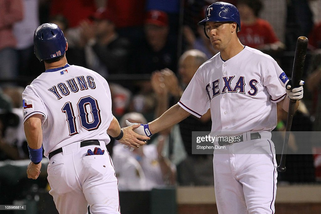 Michael Young of the Texas Rangers is congratulated by David Murphy after scoring on a sacrifice fly by Ian Kinsler in the seventh inning of Game Six...