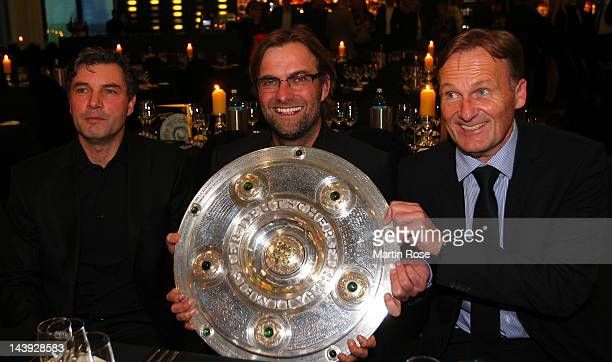 Michael Zorc manager of Dortmund Juergen Klopp head coach of Dortmund and managing director Hans Joachim Watzke pose with the trophy at View...