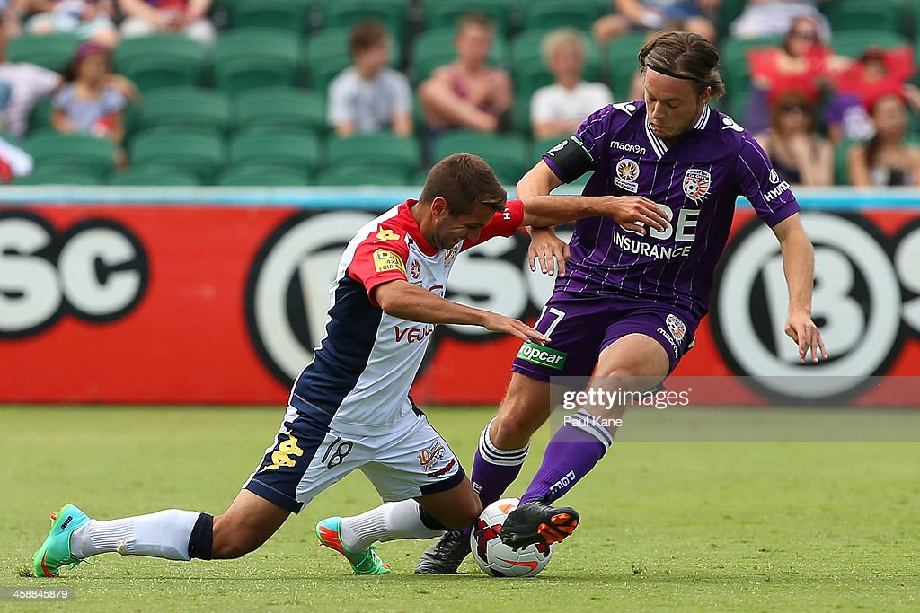 Michael Zullo of Adelaide and Chris Harold of the Glory contest for the ball during the round 11 A-League match between Perth Glory and Adelaide United at nib Stadium on December 22, 2013 in Perth, Australia.