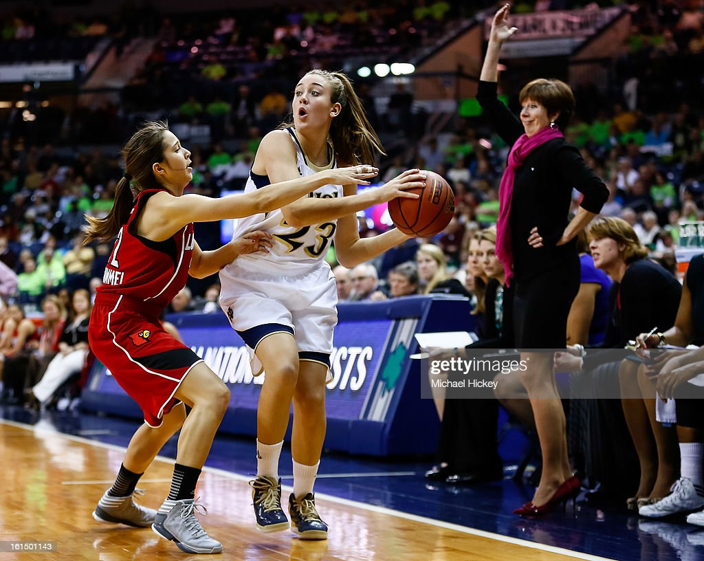 Michaela Mabrey #23 of the Notre Dame Fighting Irish holds the ball as Jude Schimmel #22 of the Louisville Cardinals guards at Purcel Pavilion on February 11, 2013 in South Bend, Indiana. Notre Dame defeated Louisville 93-64.