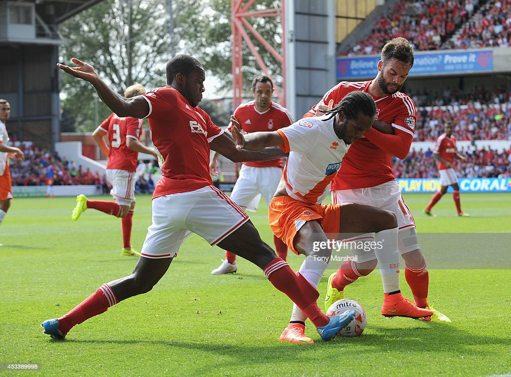 Michail Antonio (L) and Danny Fox of Nottingham Forest combine to tackle Nathan Delfouneso of Blackpool during the Sky Bet Championship match between Nottingham Forest and Blackpool at City Ground on August 9, 2014 in Nottingham, England.