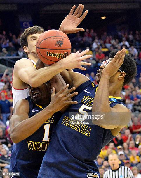 Michal Cekovsky of the Maryland Terrapins vies for posession with Jonathan Holton and Devin Williams of the West Virginia Mountaineers in the second...