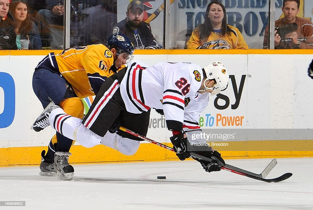 Michal Handzus #26 of the Chicago Blackhawks gets upended by Victor Bartley #64 of the Nashville Predators at the Bridgestone Arena on April 6, 2013 in Nashville, Tennessee.