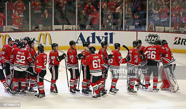 Michal Handzus of the Chicago Blackhawks hugs Corey Crawford as the rest of the team lines up for congratulations after beating the Minnesota Wild in...