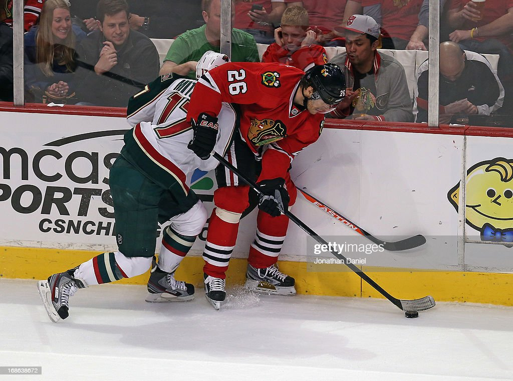 Michal Handzus #26 of the Chicago Blackhawks is hit by Torrey Mitchell #17 of the Minnesota Wild as he tries to control the puck in Game Five of the Western Conference Quarterfinals during the 2013 NHL Stanley Cup Playoffs at the United Center on May 9, 2013 in Chicago, Illinois. The Blackhawks defeated the Wild 5-1.