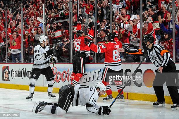 Michal Handzus of the Chicago Blackhawks jumps on the glass after scoring the game winning goal in overtime against the Los Angeles Kings as Mike...