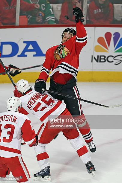 Michal Handzus of the Chicago Blackhawks leaps to knocks down the puck over Niklas Kronwall of the Detroit Red Wings in Game Five of the Western...