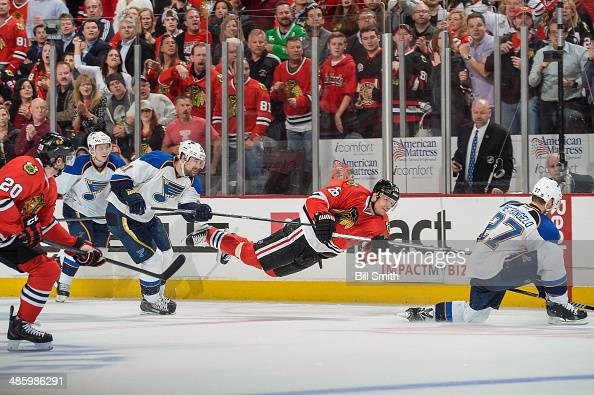 Michal Handzus of the Chicago Blackhawks shoots the puck toward an empty net as Patrik Berglund of the St Louis Blues reaches from behind in Game...