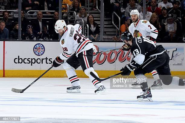 Michal Handzus of the Chicago Blackhawks skates with the puck against Kyle Clifford of the Los Angeles Kings in Game Six of the Western Conference...
