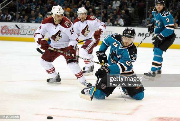 Michal Handzus of the San Jose Sharks passes the puck from his knees in front of Kyle Chipchura of the Phoenix Coyotes during an NHL hockey game at...