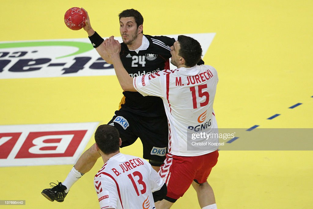 Michal Jurecki of Poland (R) defends against Michael Haass of Germany (L) during the Men's European Handball Championship second round group one match between Poland and Germany at Beogradska Arena on January 25, 2012 in Belgrade, Serbia.