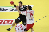 Michal Jurecki of Poland defends against Michael Haass of Germany during the Men's European Handball Championship second round group one match...