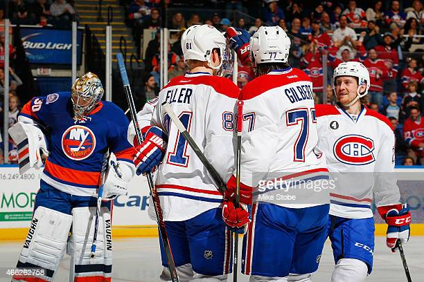 Michal Neuvirth of the New York Islanders looks on as Tomas Plekanec of the Montreal Canadiens is congratulated by his teammates after scoring a...