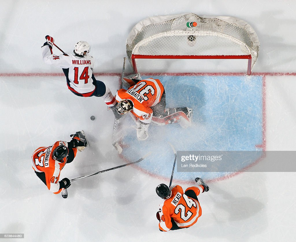 Michal Neuvirth of the Philadelphia Flyers makes a save as teammates Matt Read and Andrew MacDonald defend against Justin Williams of the Washington...