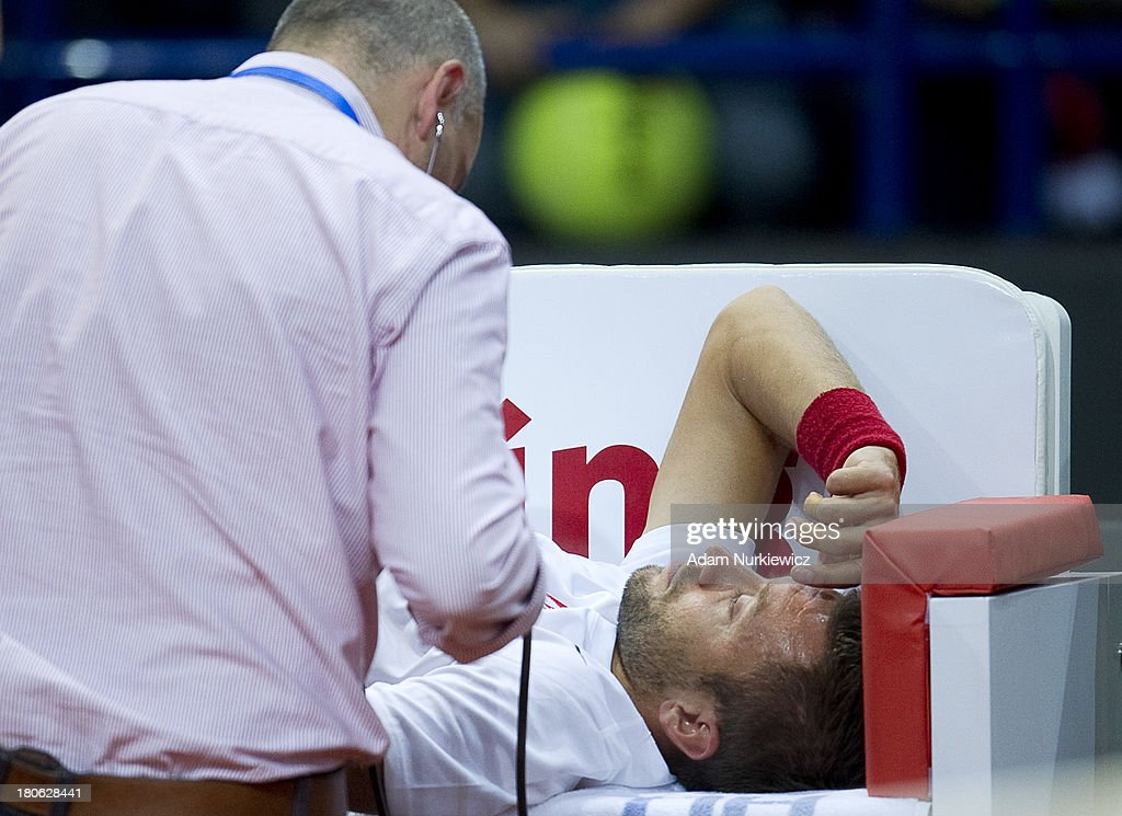 Michal Przysiezny of Poland is injued during the Davis Cup match between Poland and Australia at the Torwar Hall on September 15, 2013 in Warsaw, Poland.