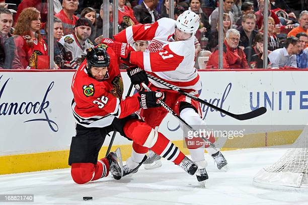 Michal Rozsival of the Chicago Blackhawks and Daniel Cleary of the Detroit Red Wings fight for the puck in Game One of the Western Conference...