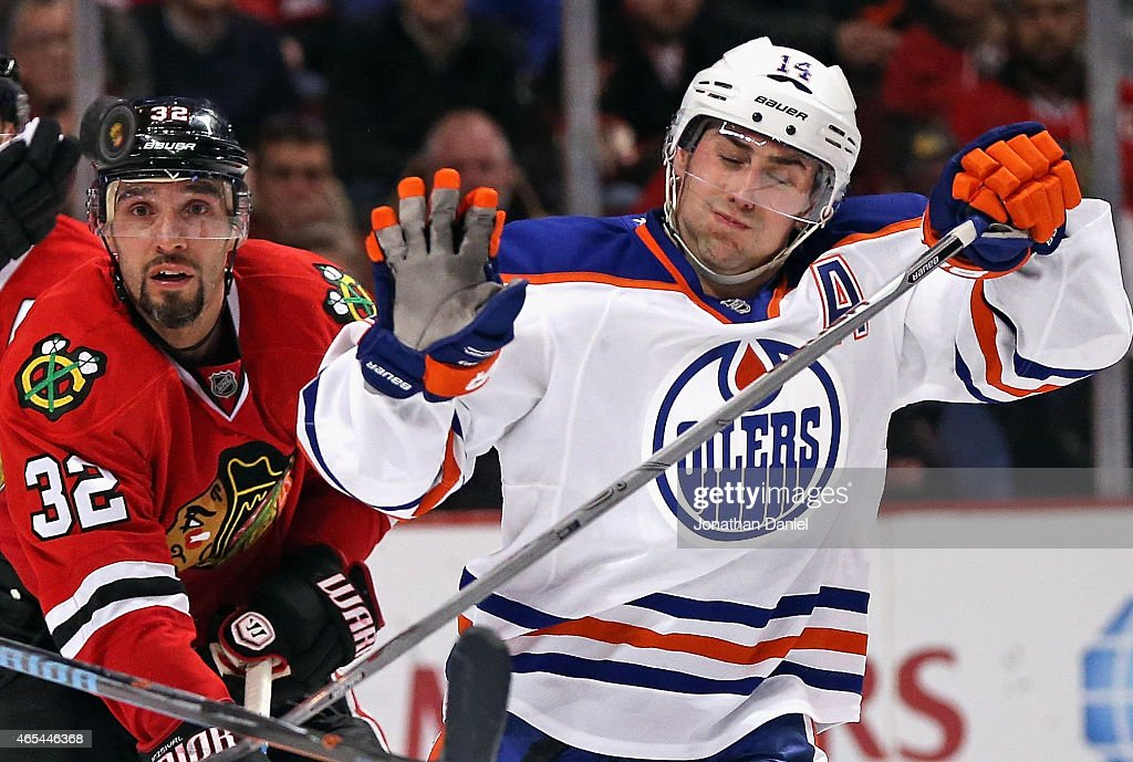 Michal Rozsival #32 of the Chicago Blackhawks and Jordan Eberle #14 of the Edmonton Oilers try to avoid a puck in the air at the United Center on March 6, 2015 in Chicago, Illinois. The Blackhawks defeated the Oilers 2-1 in a shootout.