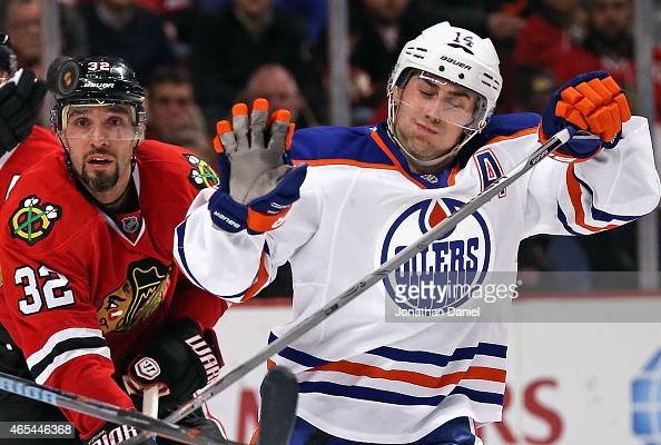 Michal Rozsival of the Chicago Blackhawks and Jordan Eberle of the Edmonton Oilers try to avoid a puck in the air at the United Center on March 6...
