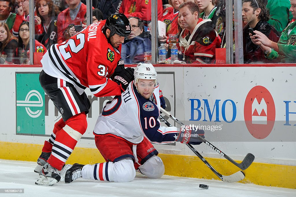 Michal Rozsival #32 of the Chicago Blackhawks and Mark Letestu #10 of the Columbus Blue Jackets fight for the puck during the NHL game on February 24, 2013 at the United Center in Chicago, Illinois.
