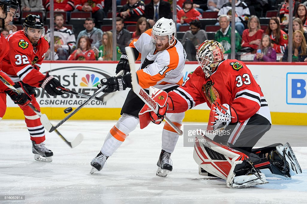 Michal Rozsival of the Chicago Blackhawks and Sean Couturier of the Philadelphia Flyers swing at the puck in front of goalie Scott Darling in the...