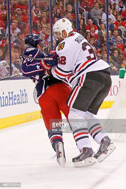 Michal Rozsival of the Chicago Blackhawks checks Corey Tropp of the Columbus Blue Jackets during the second period on December 20 2014 at Nationwide...