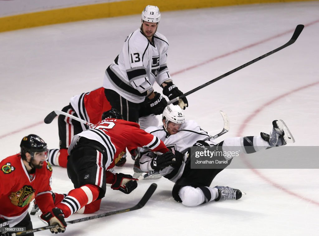 Michal Rozsival of the Chicago Blackhawks cross checks Colin Fraser of the Los Angeles Kings near the crease area in the low slot in the third period...