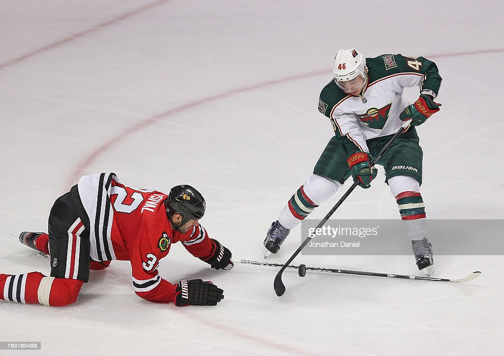 Michal Rozsival #32 of the Chicago Blackhawks drops to stop Jared Spurgeon #46 of the Minnesota Wild from shooting at the United Center on March 5, 2013 in Chicago, Illinois.