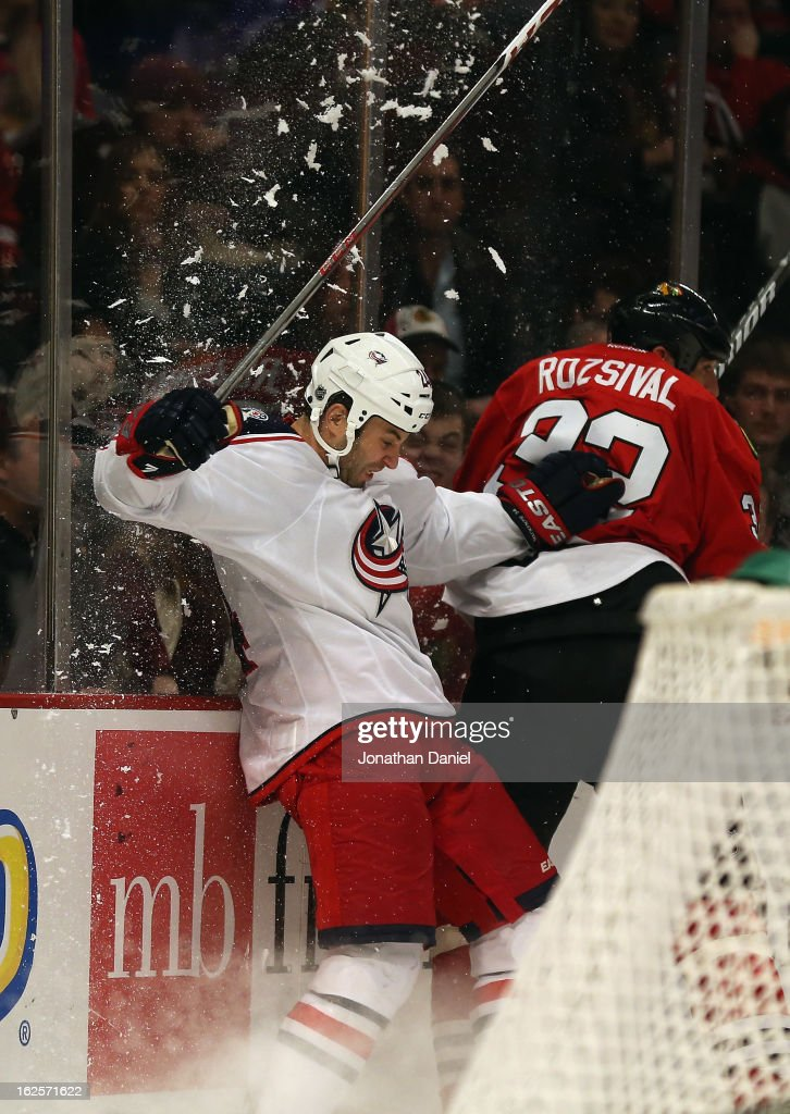 Michal Rozsival #32 of the Chicago Blackhawks forces Derek MacKenzie #24 of the Columbus Blue Jackets into the boards at the United Center on February 24, 2013 in Chicago, Illinois.