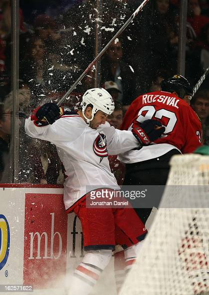 Michal Rozsival of the Chicago Blackhawks forces Derek MacKenzie of the Columbus Blue Jackets into the boards at the United Center on February 24...