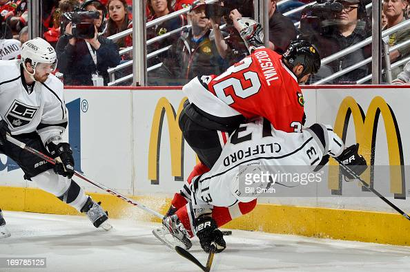 Michal Rozsival of the Chicago Blackhawks gets physical with Kyle Clifford of the Los Angeles Kings as Colin Fraser of the Kings reaches in for the...