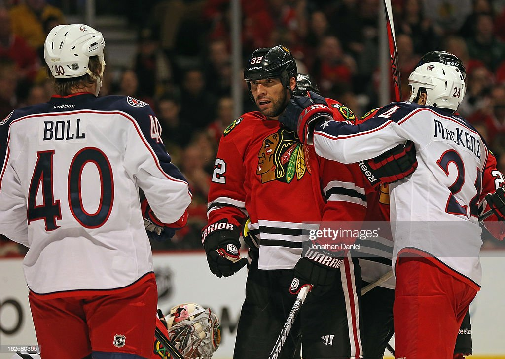 Michal Rozsival #32 of the Chicago Blackhawks is held back by Derek MacKenzie #24 of the Columbus Blue Jackets to keep him from going after Jared Boll #40 at the United Center on February 24, 2013 in Chicago, Illinois. The Blackhawks defeated the Blue Jackets 1-0.
