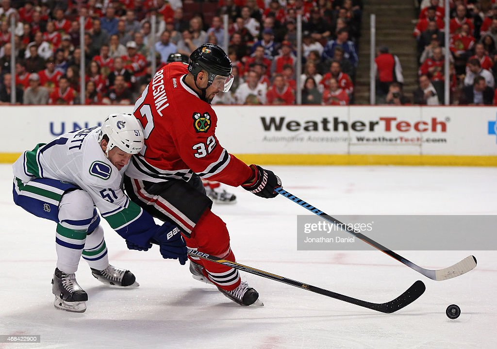 Michal Rozsival of the Chicago Blackhawks is pressured by Derek Dorsett of the Vancouver Canucks at the United Center on April 2 2015 in Chicago...