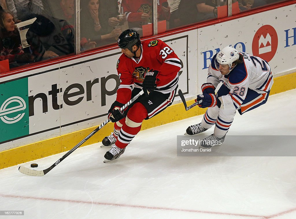 Michal Rozsival #32 of the Chicago Blackhawks is pressured by Ryan Jones #28 of the Edmonton Oilers at the United Center on February 25, 2013 in Chicago, Illinois. The Blackhawks defeated the Oilers 3-2 in overtime.