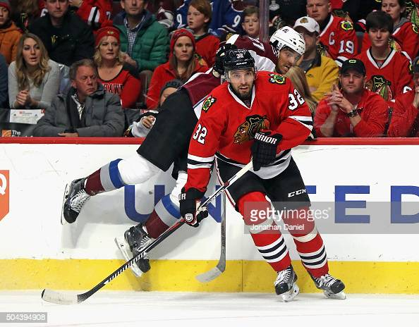Michal Rozsival of the Chicago Blackhawks pins Andreas Martinsen of the Colorado Avalanche to the boards at the United Center on January 10 2016 in...
