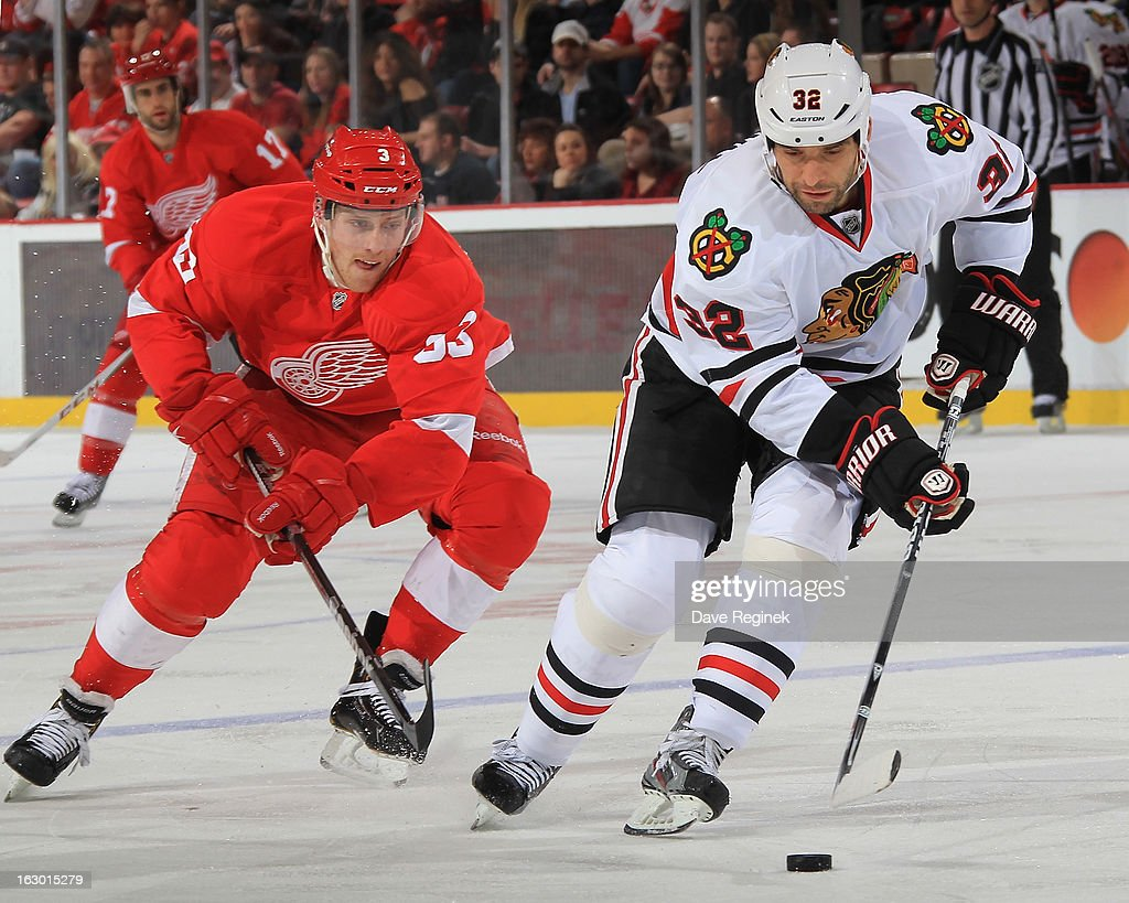Michal Rozsival #32 of the Chicago Blackhawks protects the puck from Joakim Andersson #63 of the Detroit Red Wings during an NHL game at Joe Louis Arena on March 3, 2013 in Detroit, Michigan.