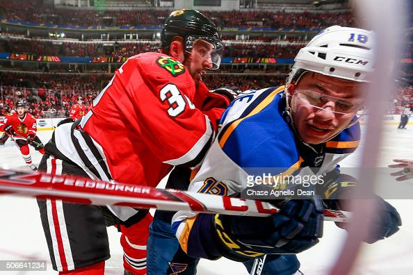 Michal Rozsival of the Chicago Blackhawks pushes into Ty Rattie of the St Louis Blues in the first period of the NHL game at the United Center on...