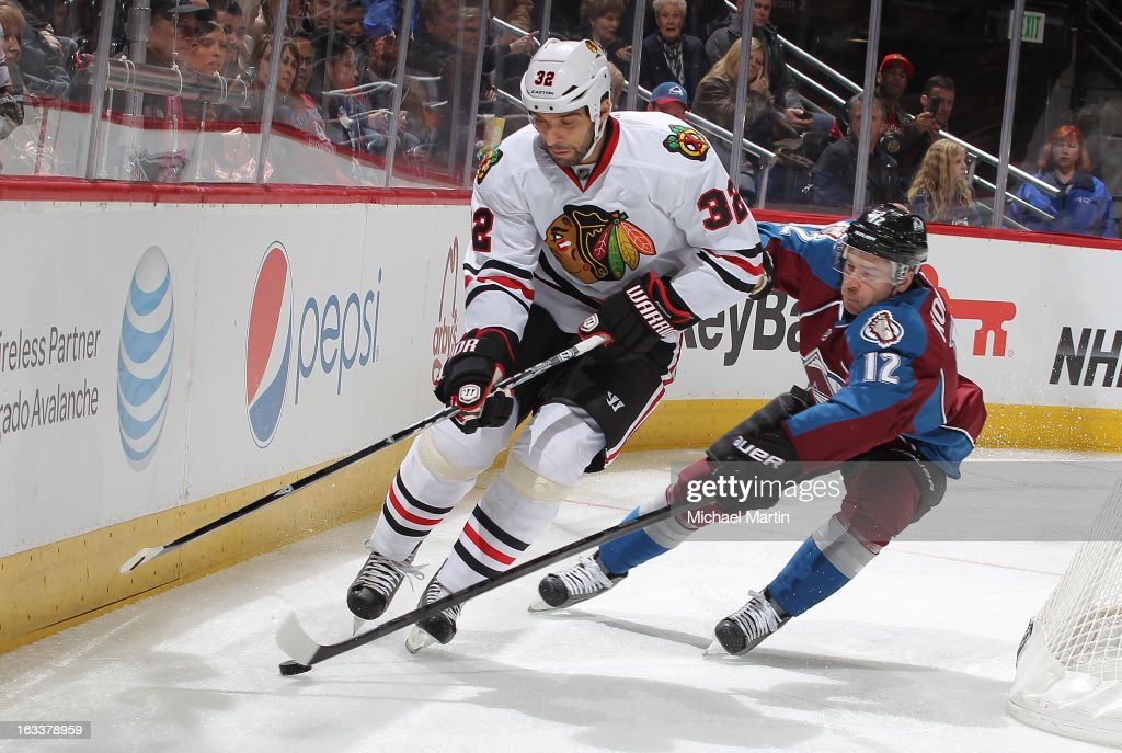 Michal Rozsival #32 of the Chicago Blackhawks skates against Chuck Kobasew #12 of the Colorado Avalanche at the Pepsi Center on March 8, 2013 in Denver, Colorado.