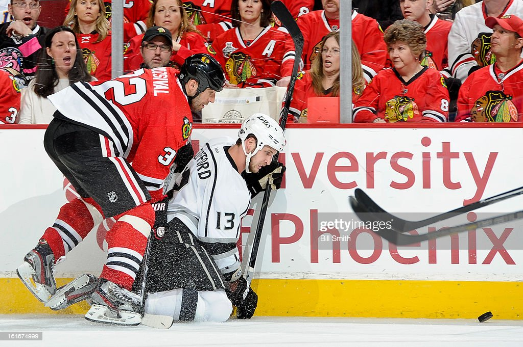 Michal Rozsival #32 of the Chicago Blackhawks skates into Kyle Clifford #13 of the Los Angeles Kings as they watch the puck by the boards during the NHL game on March 25, 2013 at the United Center in Chicago, Illinois.