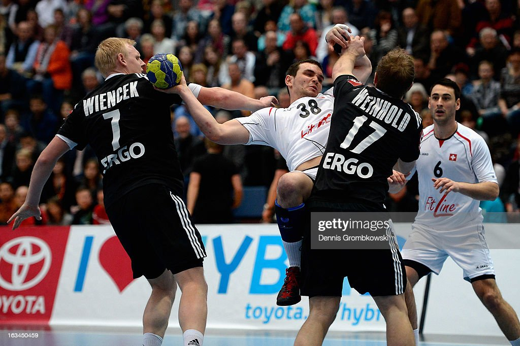 Michal Svajlen of Switzerland is challenged by Patrick Wiencek and Steffen Weinhold of Germany during the DHB International Friendly match between Germany and Switzerland at Conlog-Arena on March 10, 2013 in Koblenz am Rhein, Germany.
