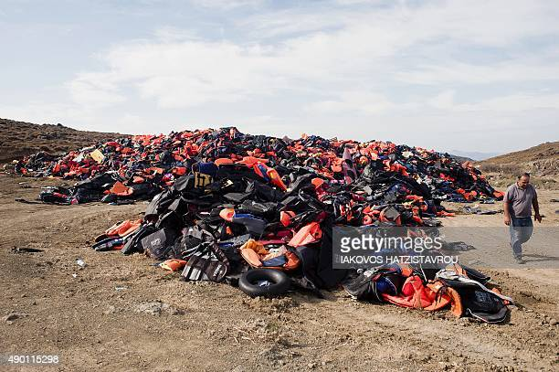 Michalis Lesbos municipality employee walks past a pile of lifejackets that were used by migrants and refugees in the village of Molyvos on the Greek...