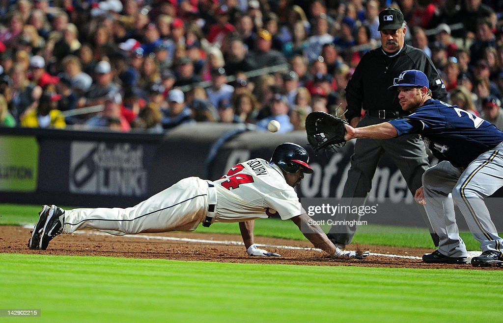 Micharl Bourn #24 of the Atlanta Braves dives back to first base against Mat Gamel #24 of the Milwaukee Brewers at Turner Field on April 14, 2012 in Atlanta, Georgia.