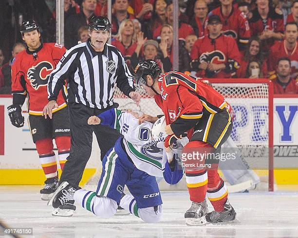 Micheal Ferland of the Calgary Flames fights Derek Dorsett of the Vancouver Canucks in the NHL season opener at Scotiabank Saddledome on October 7...